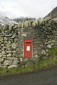 postbox set stone wall lake district snow distant fells post office royal mail uk media communications box letter red small postal cumbria cumbrian england english great britain united kingdom british