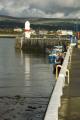 port st mary inner harbour boats lighthouse. background low dark cloud hills harbor uk coastline coastal environmental iom manx fishing storm rain isle man england english great britain united kingdom british