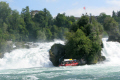 tourists leave boat climb rock middle rhine falls europe largest waterfall. swiss suisse european travel waterfall schaffhausen neuhausen switzerland schweiz