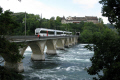 local train crosses rhine beneath schloss laufen just river reaches falls. swiss suisse european travel raliway castle switzerland schweiz europe