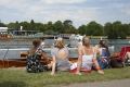 women spectators sitting river bank watching boat race royal henley regatta oxfordshire thames summer rowing boats rowboats marine row competition event water girls henley-on-thames henley on thames henleyonthames home counties england english angleterre inghilterra inglaterra united kingdom british