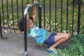 young mixed race girl playing metal bars multicultural ethnic minority summer child children play fun amusement