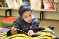 young asian boy lying bean bag library reading book multicultural ethnic minority concentration child children education learning asians books libraries
