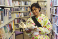 asian woman looking book standing bookshelf library multicultural ethnic minority asians choice search books libraries