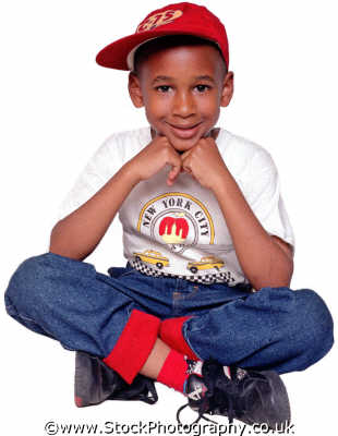 boy red baseball cap sitting cross legged boys male child males masculine manlike manly manful virile mannish people persons new york city confident relaxed negroes black ethnic portraits