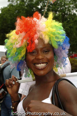 black lesbian woman smiling multi coloured afro wig gay women lesbians queers dykes female sexuality sexually attractive attraction females feminine womanlike womanly womanish effeminate ladylike people persons westminster london cockney england english angleterre inghilterra inglaterra united kingdom british