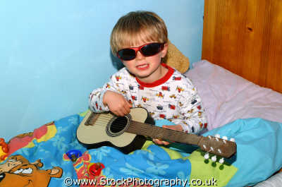 boy bed wearing sunglasses playing guitar matthew boys male child males masculine manlike manly manful virile mannish people persons middlesex middx england english angleterre inghilterra inglaterra united kingdom british