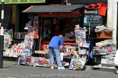 man bending news stand w1 shops shopping buildings architecture london capital england english uk magazine headline westminster cockney angleterre inghilterra inglaterra united kingdom british