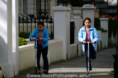 double girls scooters female children kids juveniles infants females feminine womanlike womanly womanish effeminate ladylike people persons twins play kensington chelsea london cockney england english angleterre inghilterra inglaterra united kingdom british