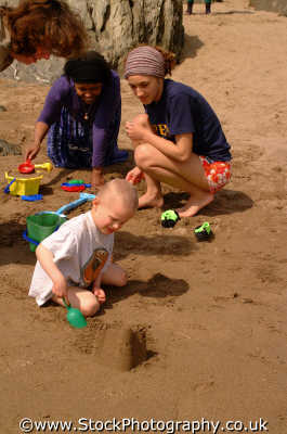 multicutural extended family building sandcastles multicultural ethnic people persons beach matthew devon devonian england english angleterre inghilterra inglaterra united kingdom british
