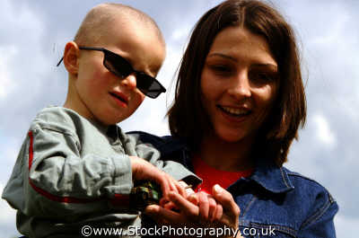 woman holding boy sunglasses matthew boys male child males masculine manlike manly manful virile mannish people persons parents parenting england english angleterre inghilterra inglaterra united kingdom british