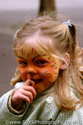 little girl tiger face paint biting finger girls female children kids juveniles infants females feminine womanlike womanly womanish effeminate ladylike people persons makeup london cockney england english angleterre inghilterra inglaterra united kingdom british