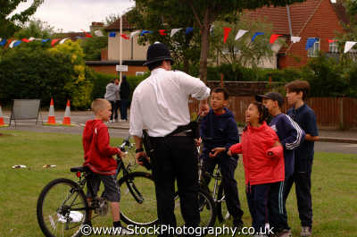 community policeman shows young children handcuffs police cops uk emergency services metropolitan ealing london cockney england english angleterre inghilterra inglaterra united kingdom british