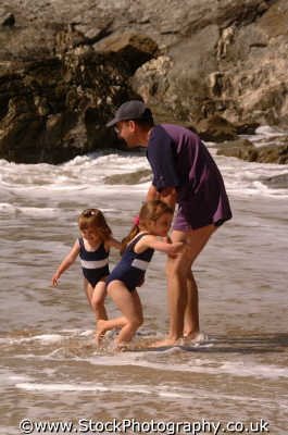 father daughters paddling sea fathers dads pops offspring parents children generations parentage parenting families family kin kinfolk tribe geneaology people persons beach holidays newquay cornish cornwall england english angleterre inghilterra inglaterra united kingdom british