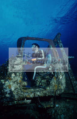 diver mimicking driving truck underwater. toyota blue belt wreck sha su adi reef sudan red sea. 2399 gross tons went aground 2/12.77 2 12 77 21277 pulled rescue tugs 5/12/77. 5 12 77 51277 spilled deck sand 15 metres. wrecks seascapes scenery scenic underwater marine diving africa sudanese