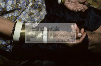 traditional heavy brass bracelets womens forearms mompilis longhouse rungus tribe kadazan people near kudat sabah. borneo malaysia. indiginous asian travel malaysia asia malaysian