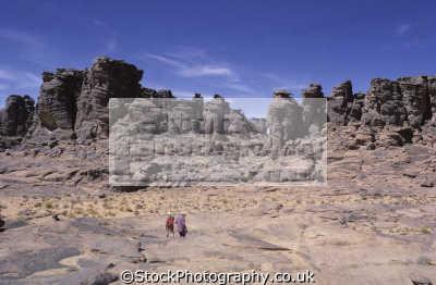 trekkers approaching tamrit tassili ajjer plateau djanet central sahara desert algeria africa. rock eroded wind sand. african travel trekking desolation africa algerian