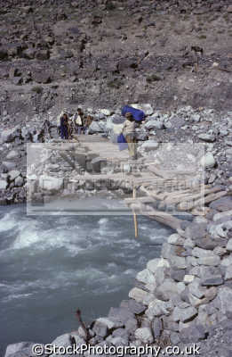 porters crossing precarious narrow log footbrige fast-flowing fast flowing fastflowing gilgit river tributary indus cross time sargus northwest pakistan asia hindu kush pakistani asian travel