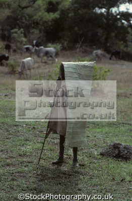 boy cattle herder wearing rain cover woven reeds near tissisat waterfalls blue nile ethiopia africa indiginous people african travel shelter ethipopia ethipopian