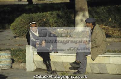 elderly uzbeki man traditional clothing chatting friend registan square samarkand uzbekistan. asia indiginous people asian travel uzbekistan uzbekistani
