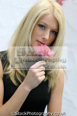 young blonde woman smelling flower blondes pigment pheomelanin yellow colour color women female females feminine womanlike womanly womanish effeminate ladylike people persons sniff