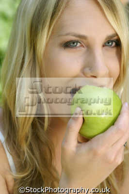 woman biting apple healthy eating nutrition balanced diet human activities people persons
