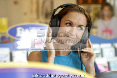 woman listening audio cd headphones music store shopping retail purchase human activities people persons