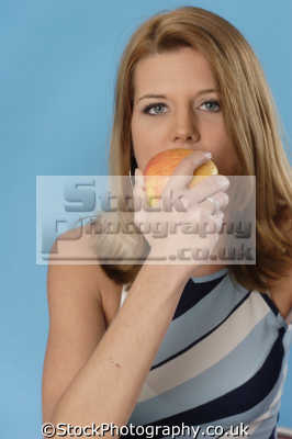 woman biting juicy apple healthy eating nutrition balanced diet human activities people persons
