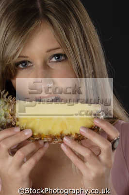 woman biting pineapple healthy eating nutrition balanced diet human activities people persons
