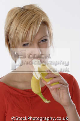 middle aged woman eating banana people mastication nutrition ingestion digestion meals food human activities persons