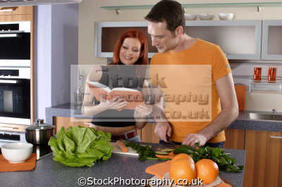 couple preparing food recipe book cooking cuisine housework domestic chores working people persons