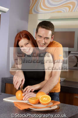 couple cutting orange together cooking cuisine housework domestic chores working people persons