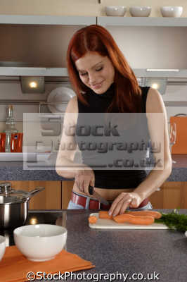 slice dice carrots sharp knife cutting board women cooking cookery cuisine meals housework domestic chores working people persons redhead ginger