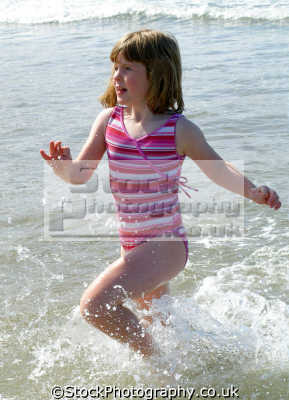 girl running sea enjoying family trip woolacombe devon. girls female children kids juveniles infants females feminine womanlike womanly womanish effeminate ladylike people persons humorous humourous humour surf splash paddle pink foam beach fun devon devonian england english great britain united kingdom british