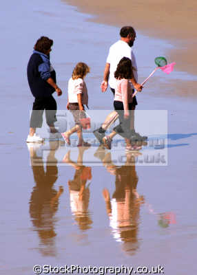 family beach westward ho devon. parents children generations parentage parenting families kin kinfolk tribe geneaology people persons humorous humourous humour fishing reflection rock pool sand net devon devonian england english great britain united kingdom british