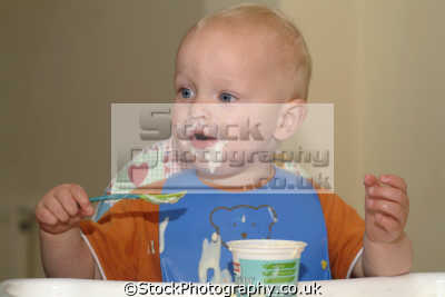 toddler pelican bib eating yoghurt getting messy people mastication nutrition ingestion digestion meals food human activities persons dirty face cornwall cornish england english great britain united kingdom british