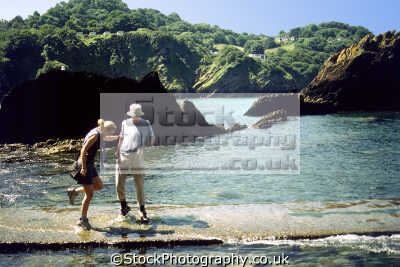 couple combe martin devon getting caught encroaching tide. uk coastline coastal environmental humorous humourous humour causeway exmoor beach devonian england english great britain united kingdom british