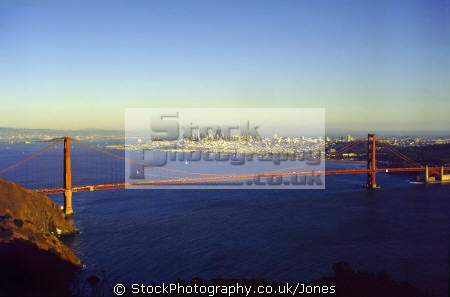 sunset golden gate bridge san francisco background oakland far distance. california american yankee travel sf bay marin peninsula county headlands alcatraz fort point franciscan californian usa united states america