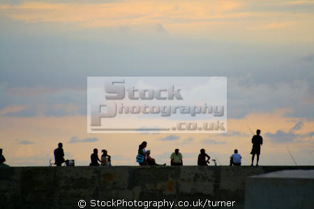 shot havana malcon sea wall people relaxing sunset. human activities persons havanan cuba chill relax fishing caribbean oceans cuban