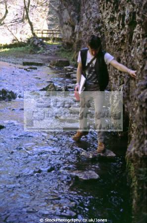 walker using stepping stones cheedale derbyshire uk rivers waterways countryside rural environmental river gorge hiker rambling limestone buxton disused railway peak district england english great britain united kingdom british