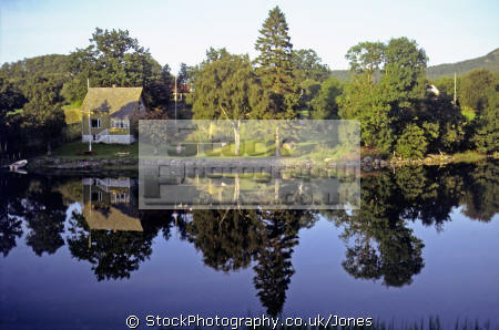 interesting reflections evening sun. taken island tysnesøy norway. european travel norge tysnesoy mirrored symmetrical house cabin idyllic lake trees norway kongeriket europe norwegan