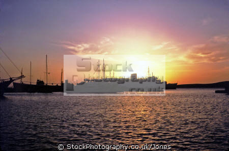 mix modern traditional greek shipping silhouetted setting sun paros harbour. european travel ferry liner fishing boat caique sunset twilight evening aegean cyclades greece europe