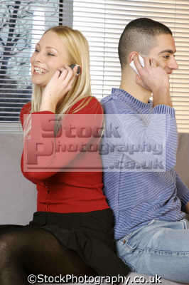 young couple home cellphones mobile phones cell-phones cell phones cellphones males masculine manlike manly manful virile mannish people persons cellular communication