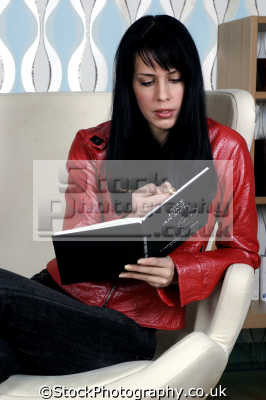 woman black hair red leather jacket writing book women female females feminine womanlike womanly womanish effeminate ladylike people persons diary
