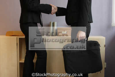women power suits shake hands people office business