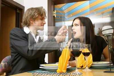man feeding woman restaurant going entertainment enjoyment human activities people persons