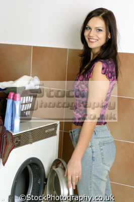 loading washing machine housework domestic chores working people persons dirty linen