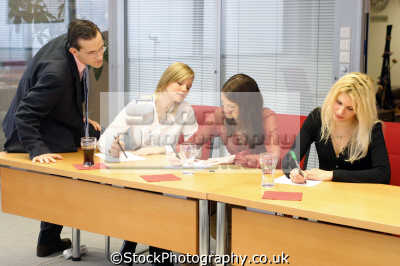male boss supervising meeting female employees people office business