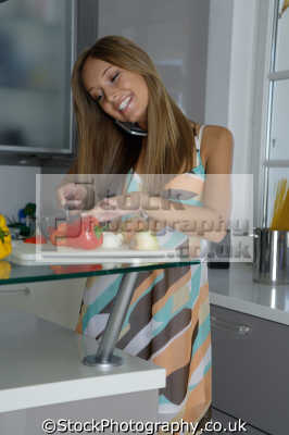 cutting red pepper phone women cooking cookery cuisine meals housework domestic chores working people persons