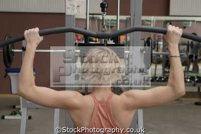 woman lifting weights gym gymnasium health clubs exercise physical athletic aerobic anaerobic fitness people persons